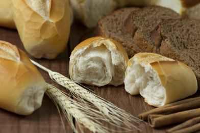 sliced bread beside wheat on table
