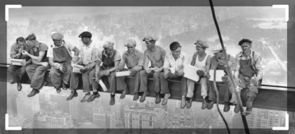 Construction workers eating lunch on top of a beam black and white photo